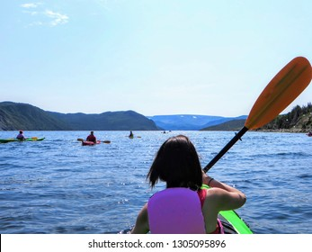 A young female tourist in a kayak exploring the beautiful waters in Bonne Bay with a group of kakayers, in Gros Morne National Park, Newfoundland, Canada.