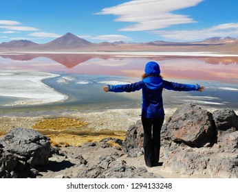 Young female tourist at Laguna Colorada, Coloured Lagoon, takes it's colour from algae and it's populated by thousands of flamingos. Andean altiplano of Bolivia, South America