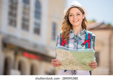 Young female tourist with map looking for a way.