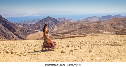 A young female tourist observing the breathtaking Panoramic view of Mount Salomon 'Har Shelomo' (Hebrew) in Eilat Mountains and the Gulf of Aqaba, Red Sea, South Israel