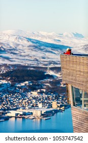 Young female tourist on snowy winter day outdoors enjoying views over Tromso Norway