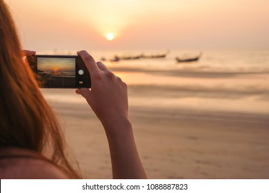 young female tourist is photographing a golden sunset with smartphone during traveling the world