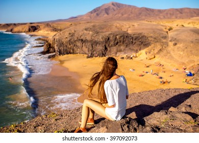 Young female tourist sitting and enjoying beautiful view on Papagayo beach on Lanzarote island in Spain