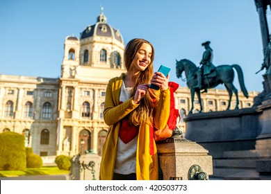 Young female tourist with smart phone on Maria Theresa square near museum of Natural history in Vienna.