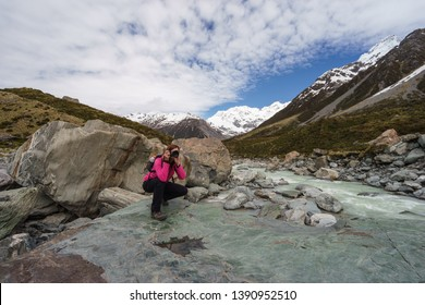 Young female tourist in softshell jacket taking photos of the amazing scenery of the Hooker Lake ath the Hooker Valley of Aoraki/Mount Cook National Park, South Island, New Zealand.
