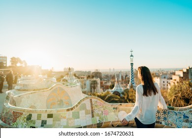 Young female tourist spending vacation in Barcelona,Catalonia,Spain.Traveling to Europe,visiting Parc Guell UNESCO site famous historical landmarks.Panoramic view on entrance.Best sunrise in Barcelona