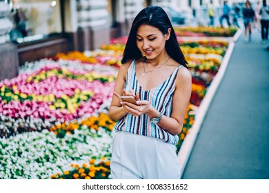 Young female tourist using application on smartphone for strolling on right direction,hipster girl browsing information of nearest cafes for recreating after city tour using mobile and internet