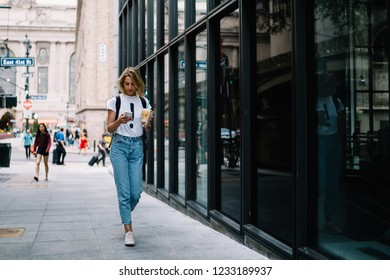 Young female tourist walking on city street with coffee takeaway checking route on mobile application, casually dressed hipster girl reading income message on smartphone strolling in downtown