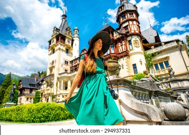Young female tourist walking on terrace near Peles castle in Romania