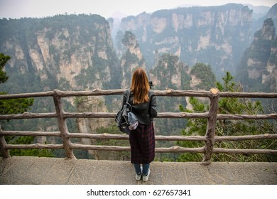 Young female tourist wear black leather jacket with gopro camera taking photo and enjoying mountain view, the Zhangjiajie National Forest Park, Hunan Province, China.
