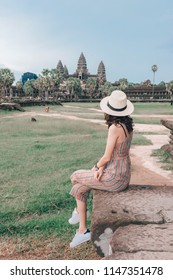 Young female tourist wearing a hat with backpack is posing at Angkor Wat temple, Siem Reap, Cambodia