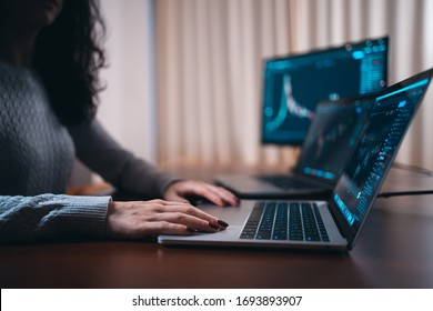 young female trader with laptop and screen looking at stock charts