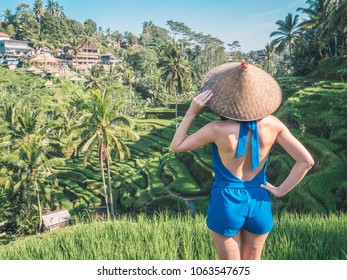 Young female in traditional Asian conical hat enjoying view on Balinese rice terraces at sunny morning in jungles. Rice terrace and travel concept.