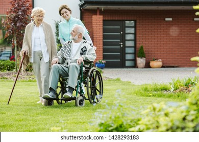 Young female trainee with elder couple in the garden