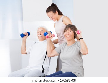 Young female trainer assisting senior couple with dumbbells at healthclub