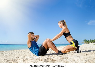 Young female trainer helping with the abs crunch at the beach