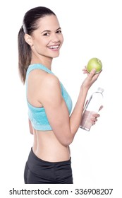 Young female trainer holding green apple