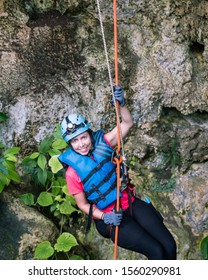 A young female traveler explores an extensive cave system in Puerto Rico and wears a helmet with a headlamp to help navigate the forests and caves of the region.