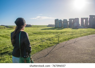 Young female traveler  and hat enjoying the view from Thailand Traveling in Stonehenge  stone monument near Salisbury, Wiltshire, UK, UNESCO World Heritage Site