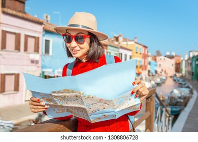 Young female traveler with hat looking at the map on the bridge on Burano island, Venice
