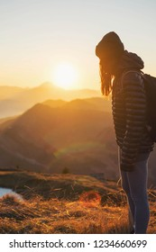 Young female traveler with long hair exploring mountains in stunning sunset looking away from the camera