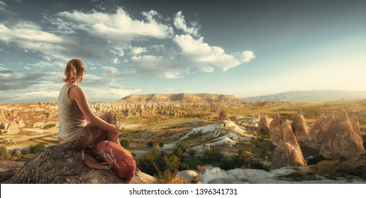 Young female traveler with red backpack enjoying watching scenic panoramic view at the hill of Cappadocia, Turkey.