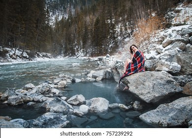 Young female traveler relaxing at natural hot springs during winter time in Lussier, BC, Canada. Pools with hot water right next to cold freezing river. Winter activities, getaway, hideout.