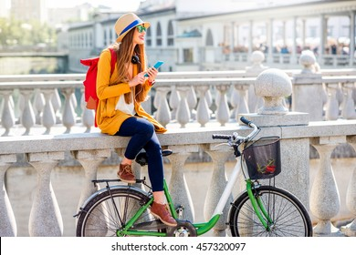 Young female traveler sitting with bicycle and using smart phone on the Triple bridge in Ljubljana. Traveling in Slovenia