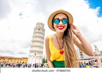 Young female traveler smiling in front of the famous leaning tower in Pisa old town in Italy. Happy vacations in Italy