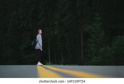 Young female traveler standing in the middle of asphalt road in the mountain woods looking at the camera. Cheerful tourist woman posing for the camera in the centre on the road beween fir forests.