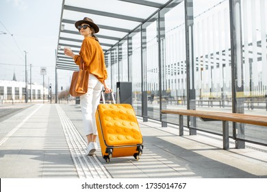Young female traveler walking with a yellow suitcase at the modern transport stop outdoors, back view. Concept of an urban transportation and travel