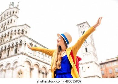 Young female traveler in yellow sweater and hat standing with raised hands in front of San Michele basilica in Lucca old town in Italy. Having great vacations in Lucca