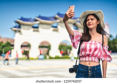 Young female travelers taking self photo with the Chiang Kai-shek Memorial Hall at main gate in Taipei, Taiwan