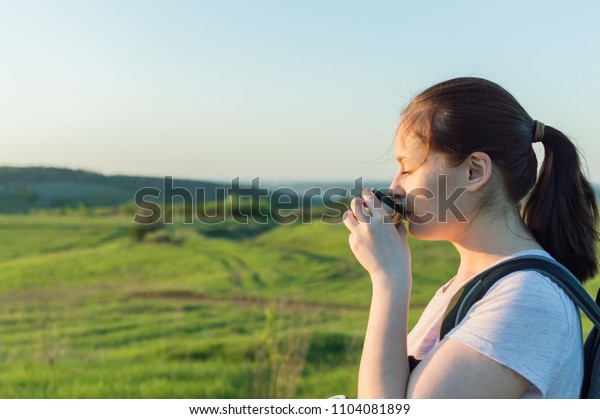 Young female traveller is drinking a coffee from the travel metallic cup in the morning. Concept of the lunch in journey, traveling, journey, hiking, backpacking.