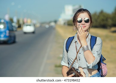 Young female traveller stays near the road or highway
