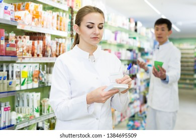 Young female in uniform is  looking medicine with notebook near shelves in apothecary