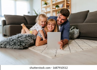 Young female using a digital tablet with her daughter and husband while lying on the floor at home