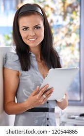 Young female using tablet computer, smiling, looking at camera.