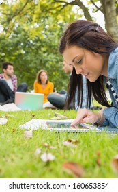Young female using tablet PC while other students using laptop in background at the park