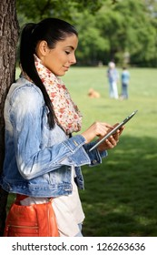 Young female using tablet, standing by tree in park, side view.