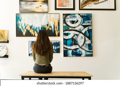 Young female visitor looking reflective while sitting on a bench and admiring the various paintings on the wall of an art gallery
