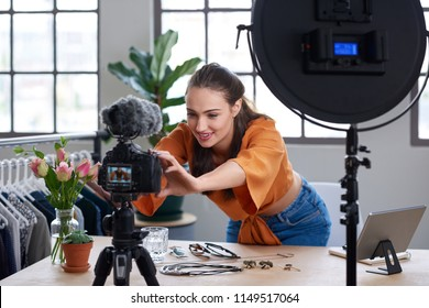 Young female vlogger adjusting her video equipment to record for her lifestyle fashion channel