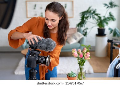 Young female vlogger adjusting her video equipment for her daily vlog video diary