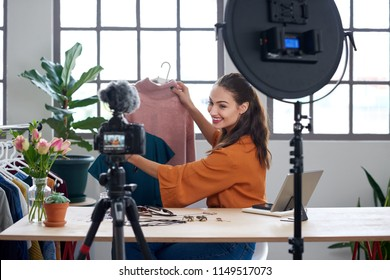 Young female vlogger recording content for her online fashion channel on social media, giving fashion advice