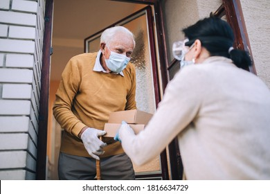 Young female volunteer in mask gives an elderly man boxes with food near his house. Quarantined, isolated. Coronavirus covid-19. Donation