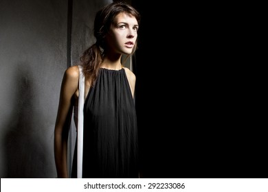Young female walking lost and alone in a dark scary street alley.  She is suspicious someone is following her from the shadows.