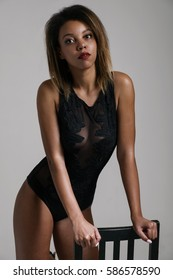 Young female wearing black bodysuit leans on chair. Vertical studio shot.