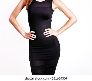 Young female wearing black dress posing in studio.