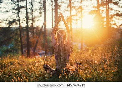 Young female wearing dreadlocks doing yoga meditation outdoors in forest, sunset on background