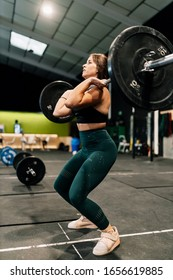 Young female weightlifter exercising in gym